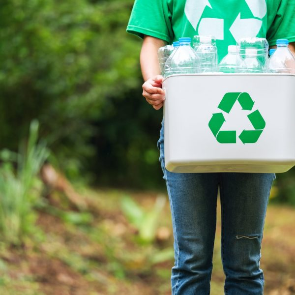 A woman holding a recycle bin with plastic bottles in the outdoors