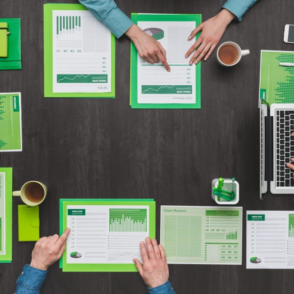 Business team working at desk and examining green financial reports, eco business, ecology and finance concept
